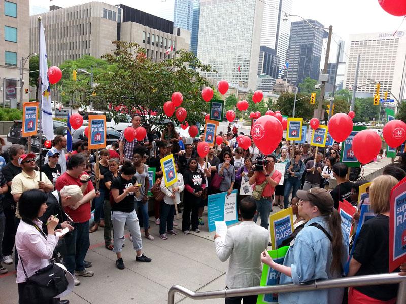 安省提高最低工資聯盟在省府勞工廳門口集會,向自由黨省政府呼籲,提高安省最低時薪至14元。