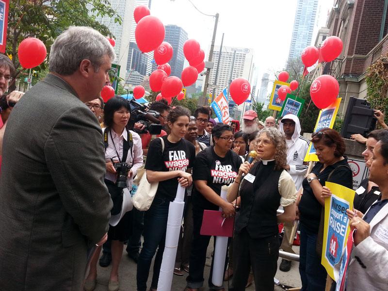 加拿大聖公會(Anglican Church of Canada)的代表Maggie Helwig向勞工廳新聞負責人Tom Zach(右)講述,現在最低工資的標準仍無法讓他們自食其力。