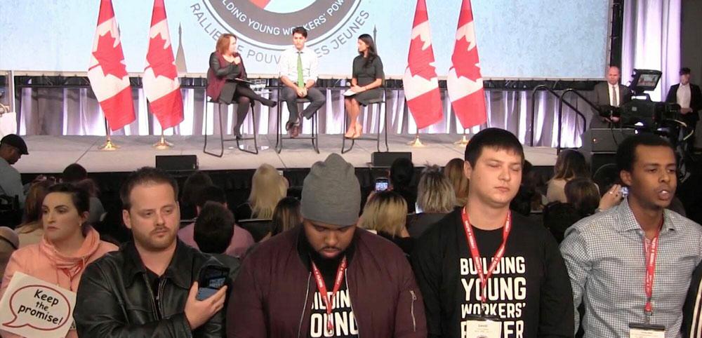 青年工人站起來背向杜魯多